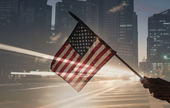 American flag us against modern city background.