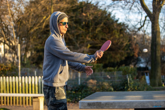 man playing table tennis in the park at sunset