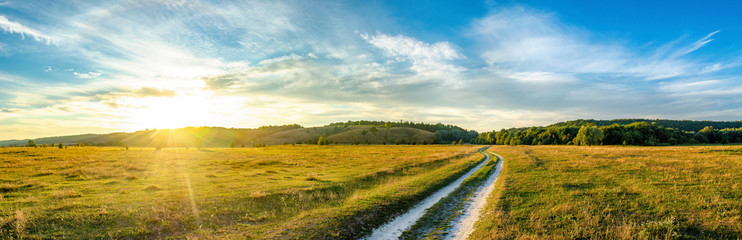 Wide photo with stunning sunset with hills on the background and the countyside road at the center of a frame