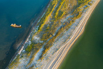aerial view to narrow shallow with old ship wreck