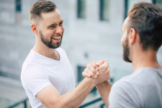 Men's friendly handshake. Two young bearded handsome friends in casual t-shirts are posing together on the city background.