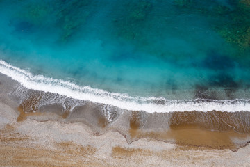 Top view of the sea shore with azure water and a sandy beach. Aerial view of the middle earth sea with coastline. Beautiful tropical sea in summer season, shot from drone