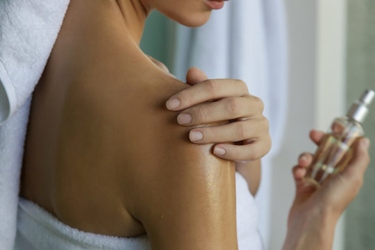 Woman applying body oil to moisturize her skin after shower, beauty skin care concept