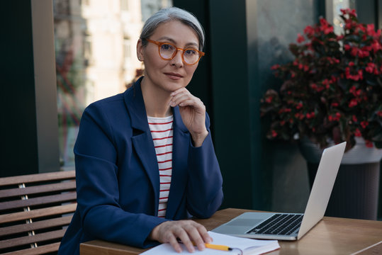 Pensive mature business woman looking at camera, sitting at workplace. Portrait of beautiful middle aged freelancer working, using laptop, planning project