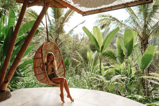 Tourist woman swing on wicker rattan hang chair in the jungle, nature view