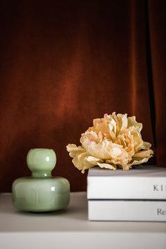 Still life vase, flower and books on brown velvet background