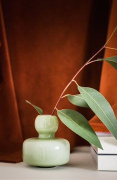 Still life of a green glass vase and gum leaves