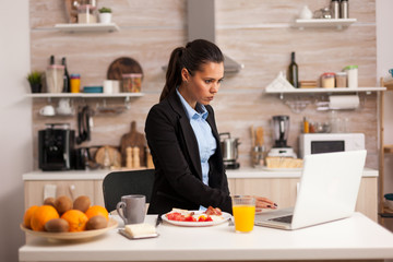 Concentrated business woman working at laptop from home in the kitchen. Freelancer in the morning multitasking in the kitchen before going to the office, stressful way of life, career and goals to