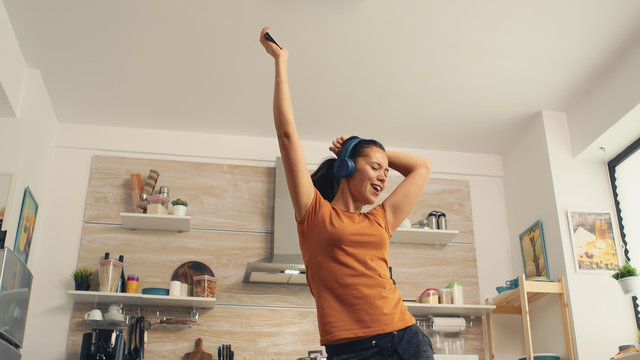 Cheerful woman singing in the kitchen in the morning. Energetic, positive, happy, funny and cute housewife dancing alone in the house. Entertainment and leiuse alone at home