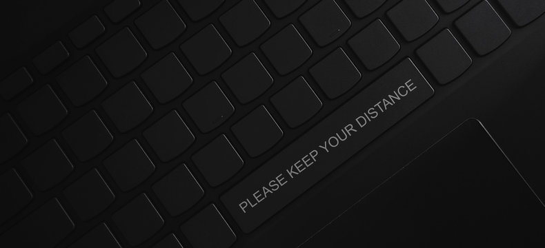 please keep your distance word on the space bar button of the keyboard. social distancing concept.