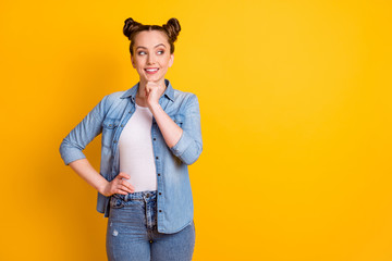 Photo of attractive pretty teen lady two buns hairdo hold smart student college university look interested side empty space minded wear casual denim shirt isolated yellow color background