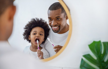 Portrait of happy family black African American father and son child boy brushing teeth in the bathroom. Morning routine with toothbrushes, father's day concept
