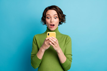 Portrait of astonished blogger girl use smartphone read incredible social network information...