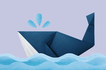 Photo of paper origami marine blue whale in waves on violet background