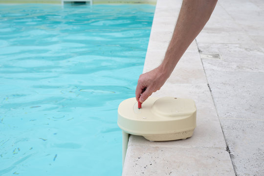 mans hand with contact key used to deactivate swimming pool alarm