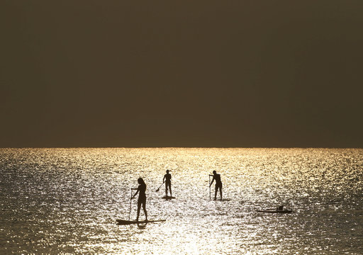 People paddle on a stand-up board during sunrise in a beach in Larnaca