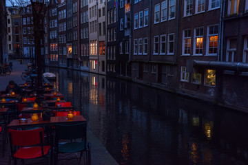 Fotobehang - Night photo of the street of Amsterdam. Cafe tables on the bank of the canal and the building in the water. Amsterdam. Europe.