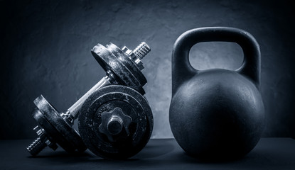 Sports dumbbells and kettlebell on a dark background