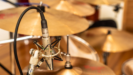 A vintage pencil microphone in place for recording drums in a recording studio setting