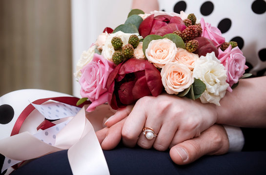 bride and groom hold hands,  bride  bouquet of maroon and white roses,  flowers