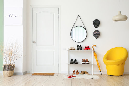Stylish interior of modern hall with shoes on stand