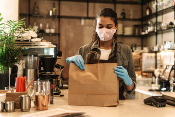 Woman with face mask standing at the counter