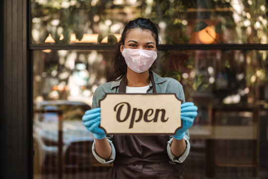 Woman coffee shop owner with face mask opens