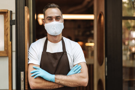 Young man cafe owner with face mask opens