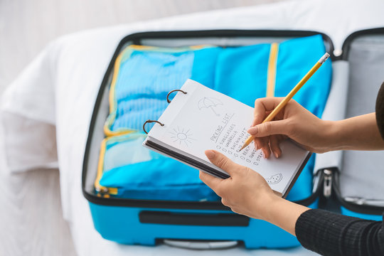 Woman making check-list of things to pack for travel at home