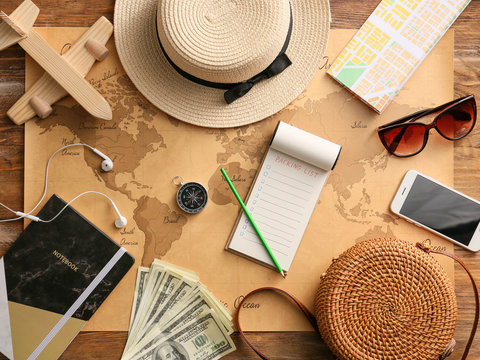 Notebook with check-list of things to pack for travel on world map