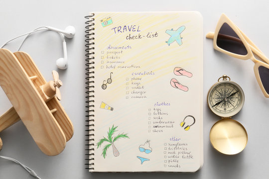 Notebook with check-list of things to pack for travel on light background