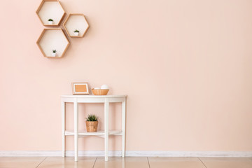 Table with decor near color wall in room