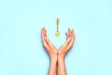 Female hands with key on color background