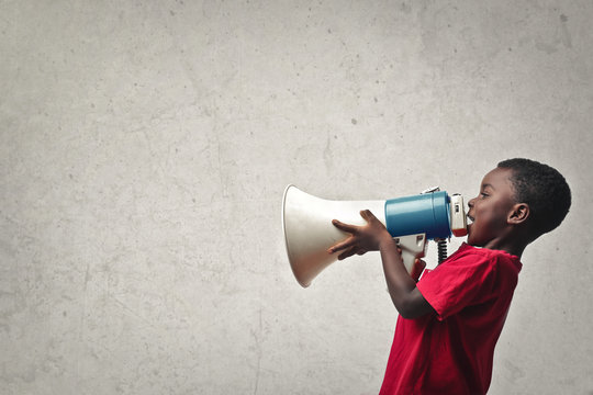 .portrait of child yelling into a megaphone