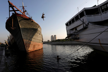 Boy jumps from a ship while playing at Sunda Kelapa port in Jakarta