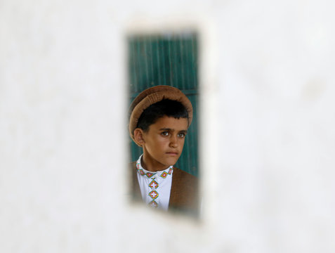 An Afghan boy is reflected in a mirror as he stands at his house after floods in Charikar, capital of Parwan province