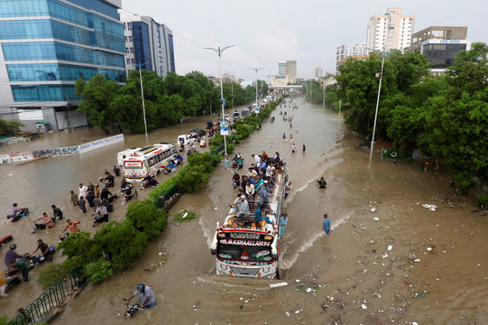 People sit atop a bus roof while others wade through the flooded road during monsoon rain, as the outbreak of the coronavirus disease (COVID-19) continues, in Karachi