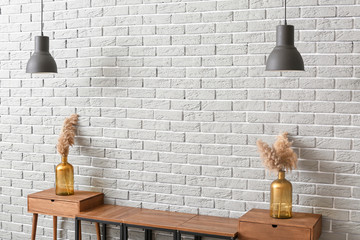 Wooden stand with decor and lamps near grey brick wall in room
