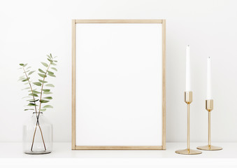 Vertical poster mockup with wooden frame, eucalyptus branches in vase and brass candle holders on empty white wall background. Minimalist Christmas interior decoration. 3d rendering, illustration.