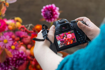 Camera on hands closeup. Making nature photo and video with autumn flowers