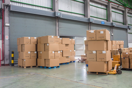 The forklift loading shipment carton boxes and goods on wooden pallet at loading dock from container truck to warehouse