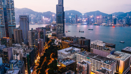 Fotomurales - Aerial scenery panoramic view of Hong Kong Evening with metropolitan bay Victoria Harbor at sunset. Lighted Modern cityscape, urban skyline buildings. Energy power infrastructure. Popular Asian city
