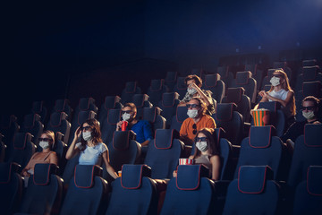 Cinema, movie theatre during quarantine. Coronavirus pandemic safety rules, social distance during movie watching. Men and women wearing protective face mask sitting in a rows of auditorium, eating