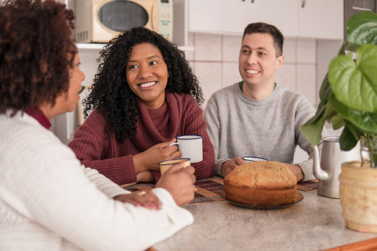 Lovely interracial couple and mother in law with cup of coffee spending time together at kitchen table, inside. Family, affectionate, reunion, together concept.