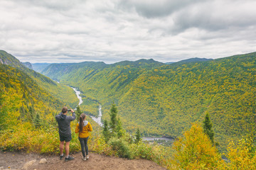 Hikers hiking in autumn outdoors sightseeing in Jacques-Cartier National Park, Quebec, Canada. Fall travel tourists walking in mountains of forest.