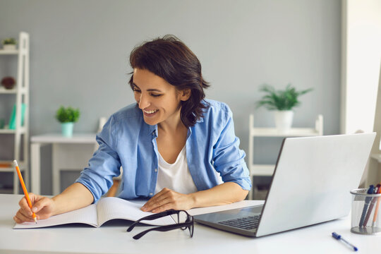 Smiling woman making notes during online lesson or meeting on laptop