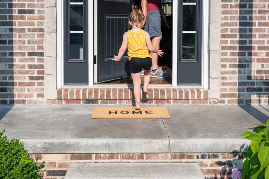 Barefoot little girl entering the front door of a home with a welcome mat that says Feels Good to be Home