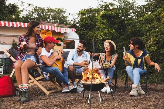 Happy friends sitting near bonfire. Camping season