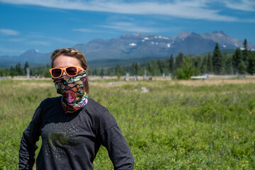 Cute, wholesome adult woman with braided hear poses in a meadow in Polebridge Montana. Neck gaiter...