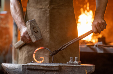 Close up blacksmith is processing a hot metal object of a spiral shape at anvil in a workshop
